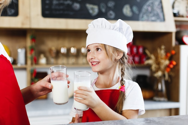 Mamá y pequeña hija encantadora se divierten bebiendo leche en la mesa en una cocina acogedora