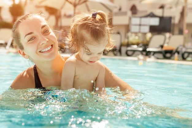Mamá y pequeña hija se juegan en la piscina abierta.