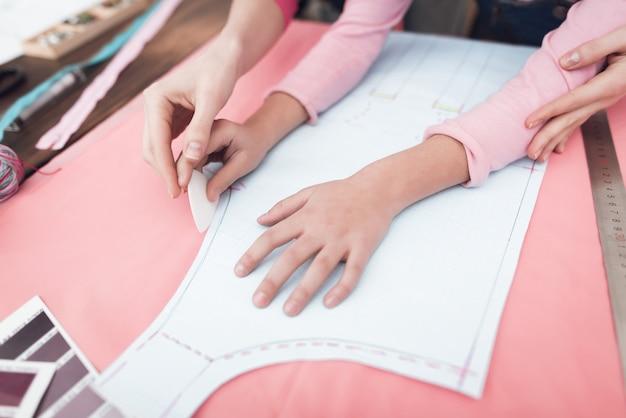 Mamá y pequeña hija juntas cosen ropa.