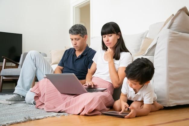 Mamá con portátil viendo a su hijo pequeño con tableta, sentado en el piso de la sala de estar por sus padres.