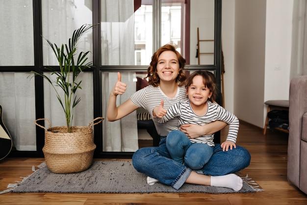 Mamá positiva y su pequeña hija traviesa se sientan en una alfombra y muestran los pulgares hacia arriba.