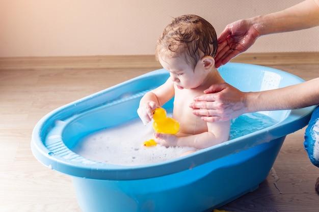 Mamá que lava al niño pequeño en un baño azul en el cuarto de baño.