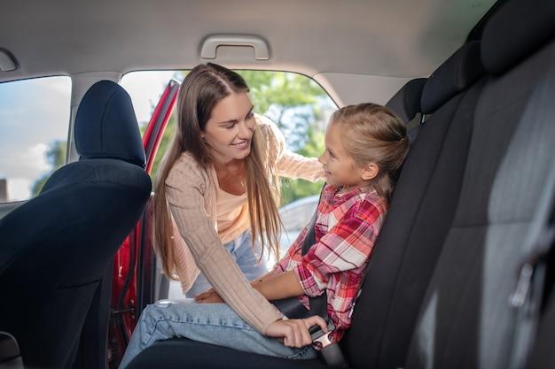 Mamá sonriente abrochando el cinturón de seguridad de su hija en el asiento trasero del coche