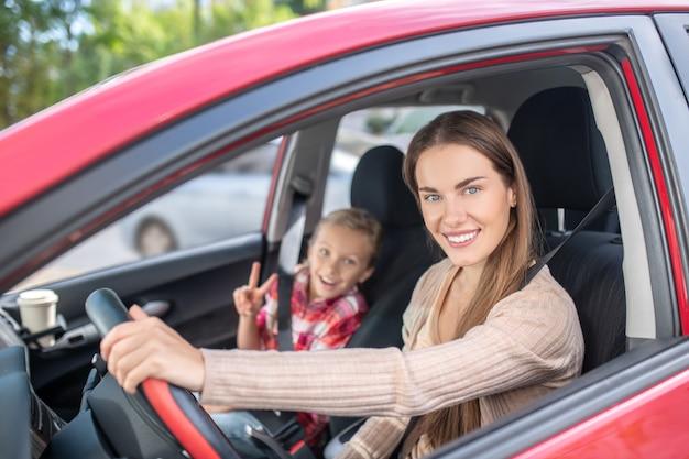 Mamá sonriente conduciendo con su hija, mostrando el signo de la paz desde el asiento del pasajero