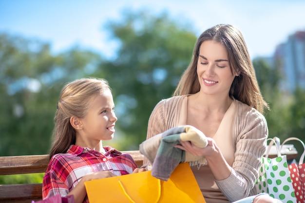 Mamá sonriente mostrando a su hija nueva bufanda en un banco del parque