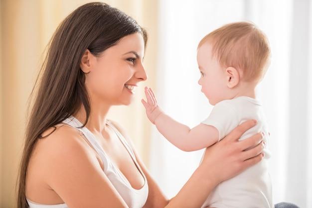 Mamá sostiene a un pequeño bebé lindo en sus brazos.