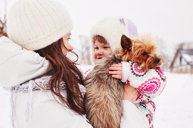 Mamá sostiene a su hija y su perrito.