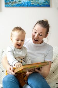 Mamá y su bebé están leyendo un libro en casa en un sofá. feliz y sonriente
