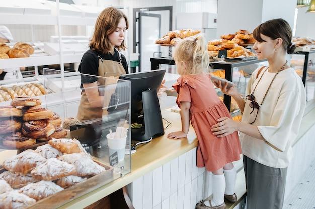 Mamá con su hija comprando pasteles en una panadería. la niña está de pie en un paso de anticipación.