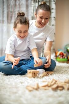 Mamá y su hija juegan juntas en casa en el piso. feliz y sonriente