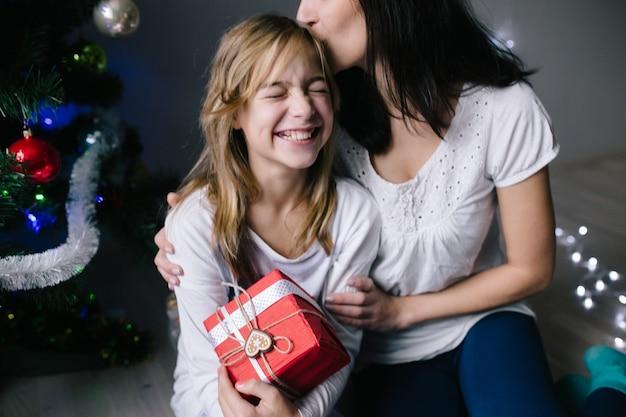 Mamá y su niña linda hija intercambiando regalos.