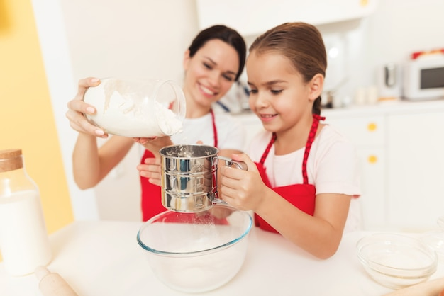 Mamá y su pequeña hija cocinan juntas en la cocina
