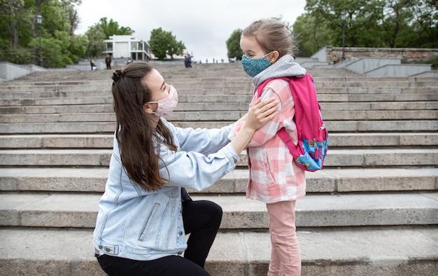 Mamá con su pequeña hija, una colegiala, en los escalones de camino a la escuela. concepto de educación sobre la pandemia de coronavirus.