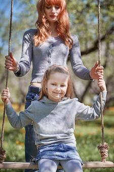 Mamá con su pequeña hija en el columpio.