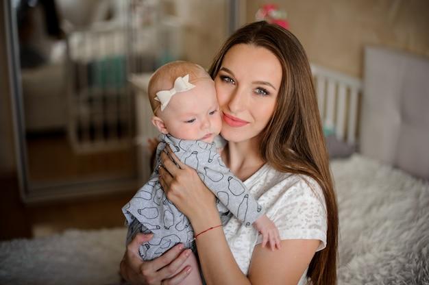 Mamá con su pequeña hija en las manos en la habitación