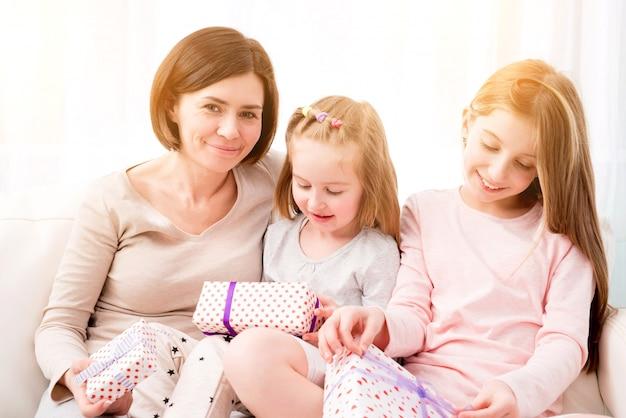 Mamá y sus hijas intercambian regalos