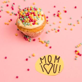Mamá te amo título en papel cerca de cupcake