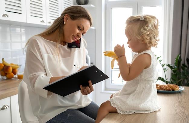 Mamá trabajando en casa con el niño durante la cuarentena