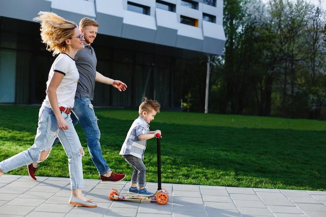Mamá y papá corren detrás de su hijo mientras él monta un patinete