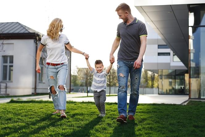 Mamá y papá dan vueltas a su hijo y se divierten caminando afuera