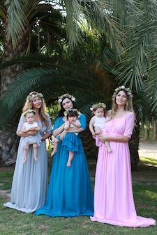 Mamás amistosas tres madres con hermosos vestidos idénticos en el parque con bebés