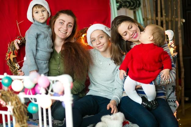 Mamás con niños colgados en una cama decorada para navidad