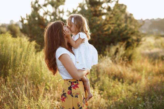 Las mamás y su hija en la naturaleza se besan en el paseo de verano