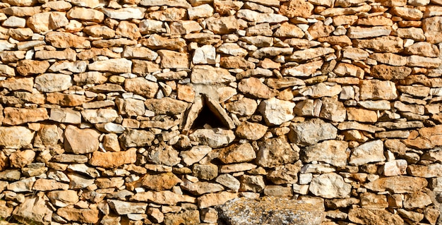 Mampostería envejecida muro de piedra triángulo ventana agujero