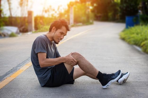 Man runner jogging para hacer ejercicio en la mañana, pero accidente dolor de rodilla mientras corre