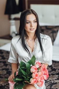 Mañana de una bella mujer en el hotel con rosas y pastel