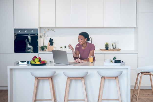 Mañana en casa. mujer joven de piel oscura desayunando en casa y viendo algo en una computadora portátil