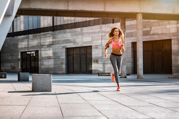 En la mañana. colocar mujer atlética corriendo en la ciudad mientras hace su entrenamiento matutino