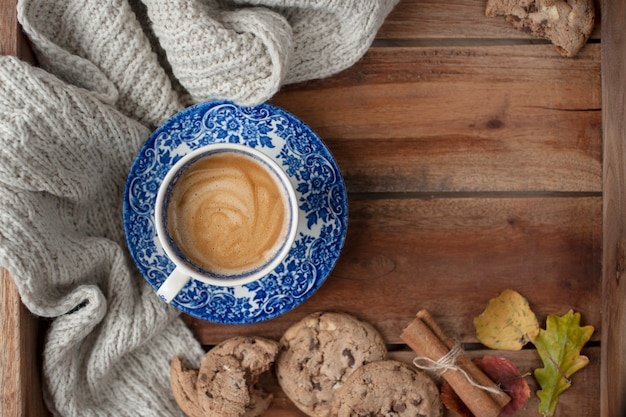 Mañana fragante y fondo de madera. galletas de galletas con chocolate para el desayuno y una tela escocesa de punto caliente. decoración de otoño vista superior. copia espacio