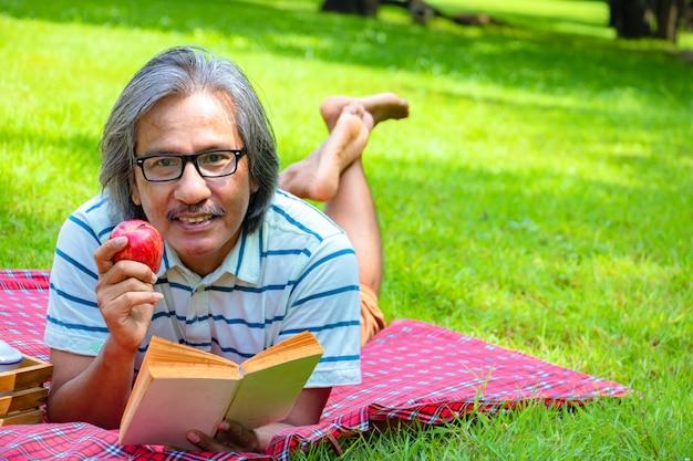 Por la mañana él está leyendo un libro con una aplicación roja. está acostado en el pasto al lado de un picnic.
