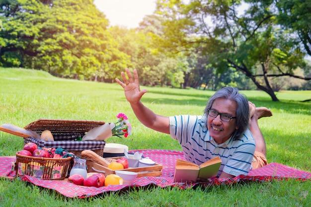 Por la mañana él está leyendo un libro, sonríe y ríe. está acostado en el pasto al lado de un picnic.