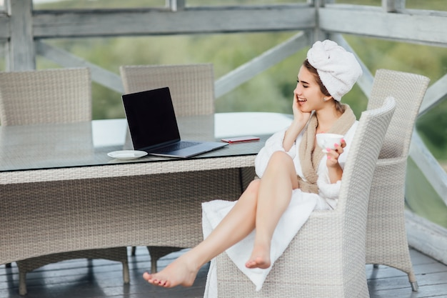 Mañana en línea. sonriente, linda mujer con su laptop en túnica blanca se sienta en la terraza.