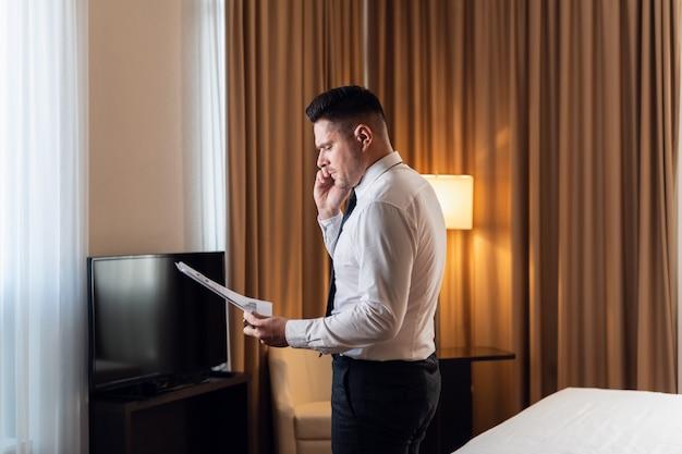 Mañana en lujoso hotel. vista lateral de un apuesto joven empresario haciendo una llamada telefónica, de pie en una pose segura en una ventana panorámica con algunos planos en la mano