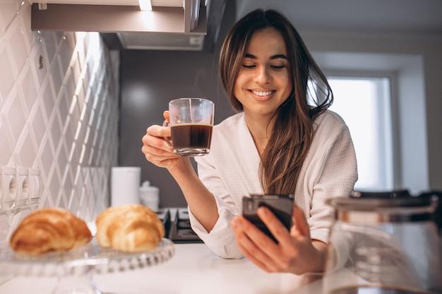 Mañana de la mujer con teléfono, croissant y café en la cocina.