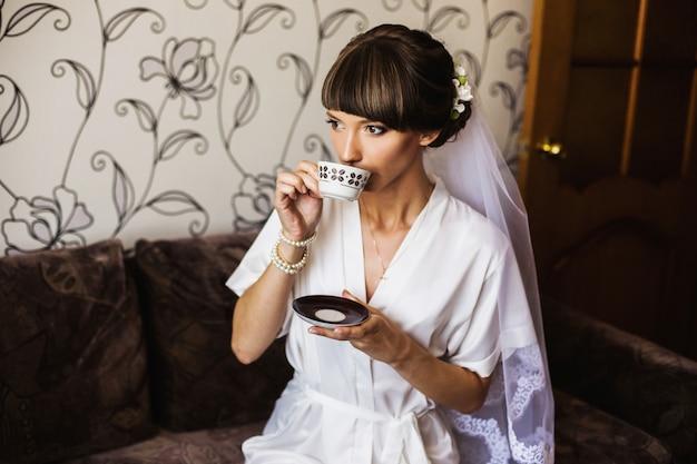 Mañana de la novia. niña bebe café de una taza blanca. ceremonia de la boda