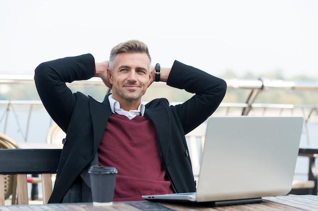 Mañana perfecta. apuesto hombre sonriente disfrutando de su café. feliz hipster sosteniendo portátil y taza de café café terraza fondo. el café me despierta por la mañana. concepto de trabajador de oficina regular.