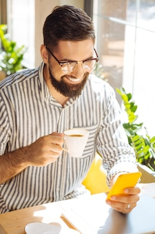 Mañana perfecta. hombre encantado feliz usando su teléfono inteligente mientras disfruta de su taza de café en la cafetería