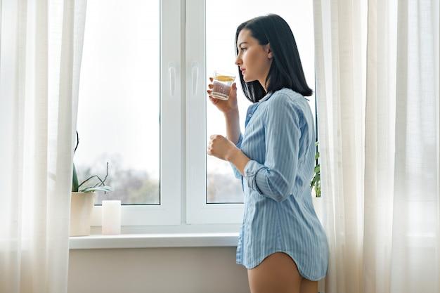 Mañana vaso de agua con limón en manos de una mujer joven