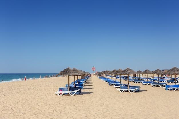 Mañana de verano en la playa de la isla de tavira. camas vacías en la arena.
