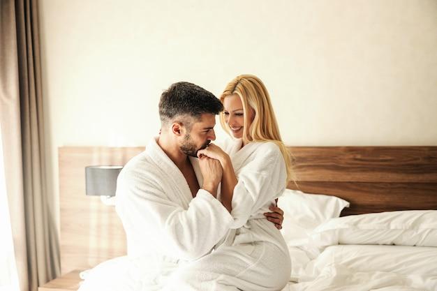 Mañanas románticas en el hotel. un hombre y una mujer vestidos con túnicas blancas y sobre las sábanas blancas de una cálida habitación de hotel abrazados en la cama. un beso en la mano femenina de una mujer, hombre machista. amor sonriendo luna de miel