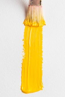 Mancha texturada de pintura amarilla cerca de pincel