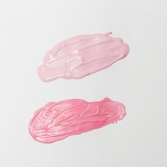Manchas de lápices labiales rosados sobre fondo gris