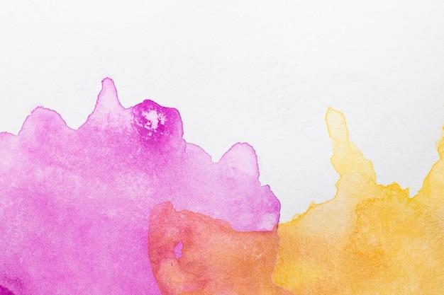 Manchas pintadas a mano en tonos violeta y naranja.