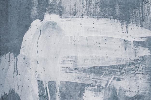 Manchas de pintura blanca sobre muro de hormigón gris.