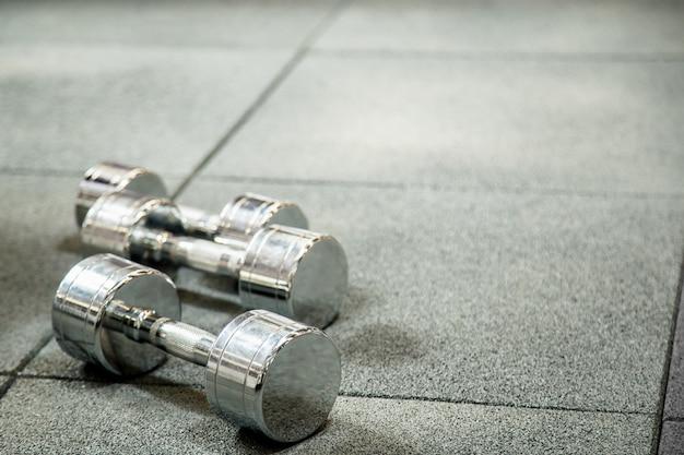 Mancuernas en club deportivo moderno. equipo de entrenamiento con pesas