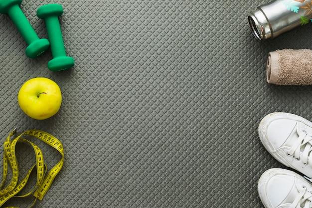 Mancuernas; manzana; cinta métrica; zapatillas de deporte; toalla y botella de agua sobre colchoneta de ejercicios